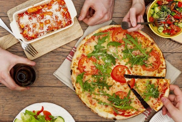 Hands grab food from table on platters and being served for local family dining guide 2020