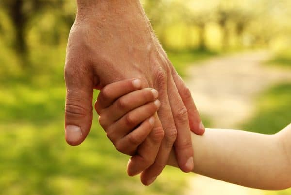 Daughter hold her father's hand outside on walk to help her through separation