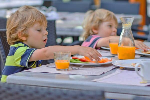 Two young boys eat food with orange juice at kid-friendly restaurant