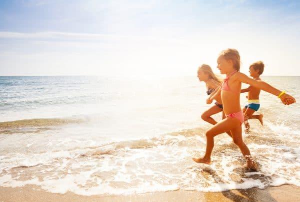 children on January school holidays run along Cairns beach