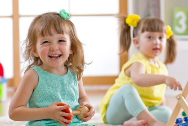 Two girls under 5 years old smile and play with tools as activity