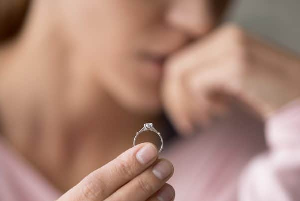 woman holds up wedding ring she has removed due to separation