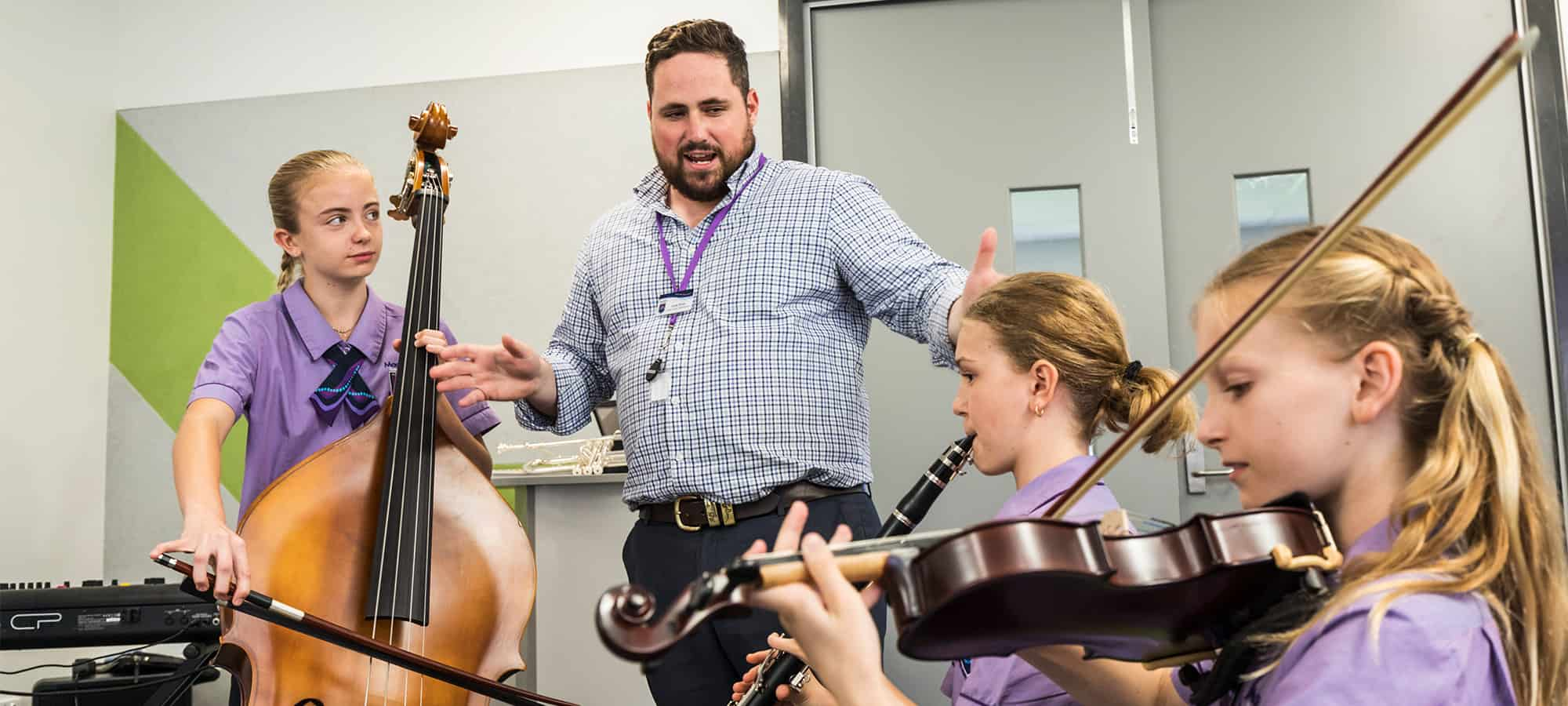 MacKillop Catholic College students play instruments with teacher